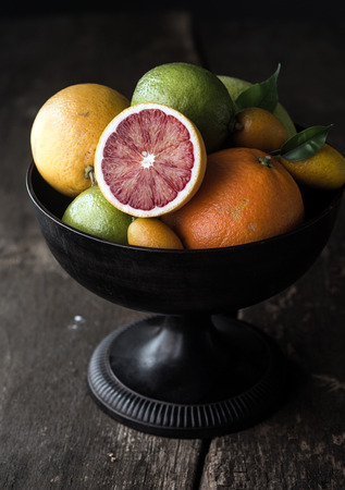 Delicious halved blood orange showing the red pulp on a citrus fruit display in a fruit bowl on an old rustic wooden table photo