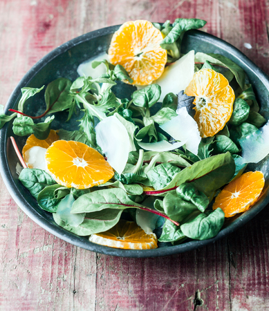 Bowl of fresh green leafy marche, sliced orange and parmesan cheese salad on a vintage wooden background, high angle view photo