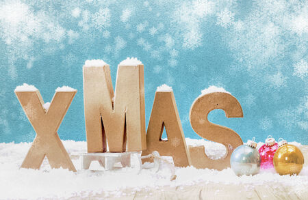 Cold wintry Xmas background with wooden letters for Xmas in snow with colorful Christmas baubles under falling snowflakes on a cool blue background with copyspace photo