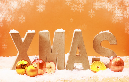 Colorful Xmas background with falling snowflakes and wooden letters spelling Xmas covered in snow with orange and gold decorations and fruit on a warm toned orange background photo
