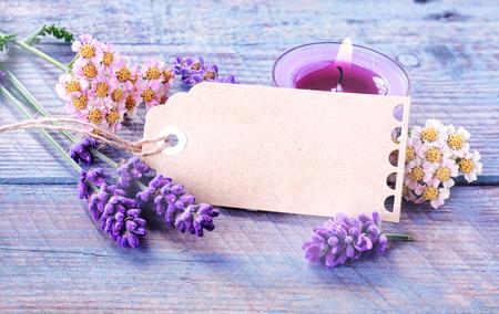 스파, 휴식과 소박한 푸른 나무 보드에 아로마 테라피 치료를위한 레코딩 촛불 신선한 라벤더 꽃 사이 copyspace 빈 선물 태그 또는 라벨과 웰빙 배경