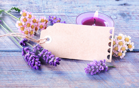 mimos: Spa, la relajación y el fondo de bienestar con una etiqueta de regalo en blanco o etiqueta con copyspace entre lavanda fresca y flores con velas encendidas para tratamiento de aromaterapia sobre rústicas tablas de madera de color azul