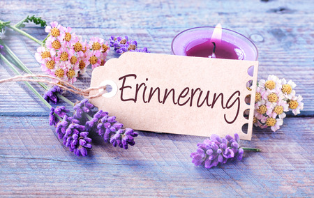 Beautiful delicate blue and lilac colored background depicting - Erinnerung - Memories - with fresh scented lavender spikes, dainty flowers and a burning aromatic candle on blue rustic wooden boards photo