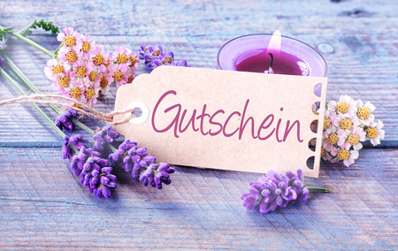 Gift tag with the word Gutschein in German on light blue wooden boards with a burning candle and scented lavender and fresh flowers in a spa and wellness concept photo