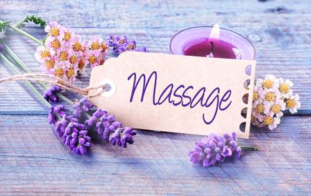 masaje: Fondo masaje Spa con lavanda fresca fragante y flores con una vela de aromaterapia quema alrededor de una etiqueta o etiquetas de regalo con el gui�n - Masaje - en los tablones azules r�sticas