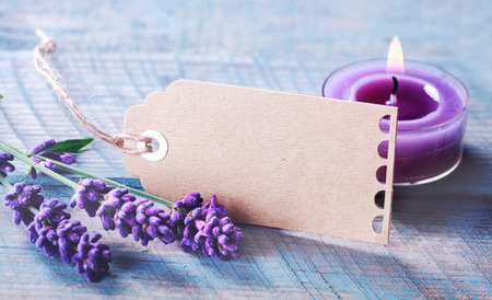 Beautiful tranquil spa and zen background with spikes of fragrant purple lavender and a burning aromatherapy candle on a rustic wooden background with a blank gift tag for your message photo