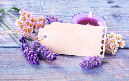Spa or wellness background with a blank decorative gift tag surrounded by dainty fresh flowers and lavender with a burning aromatherapy candle with essential oil on rustic lilac colored wooden boards