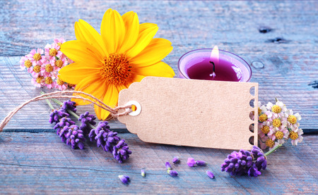 Fresh floral wellness and spa still life with spikes of scented lavender, dainty blosoms and a colourful yellow gerbera surrounding a blank gift tag with copyspace and a burning aromatherapy candle photo