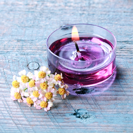 Aromatherapy spa concept with fresh white summer blossoms alongside a fragrant translucent purple burning candle with plant extracts and essential oils photo