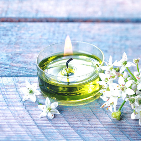 holistic therapy: Beautiful natural organic spa background with a spray of delicate white flowers alongside a burning green aromatherapy candle on a blue background in a wellness and pampering concept Stock Photo