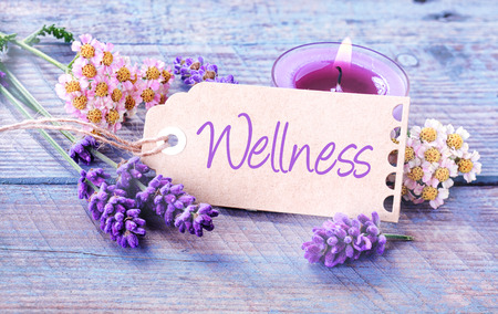 Pretty floral Wellness background with fresh scented lavender and dainty inflorescences around a label with the script - Wellness - leaning against a burning purple aromatherapy candle in a spa photo
