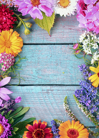Beautiful fresh floral border of assorted colorful summer flowers on blue wooden boards with vertical copyspace