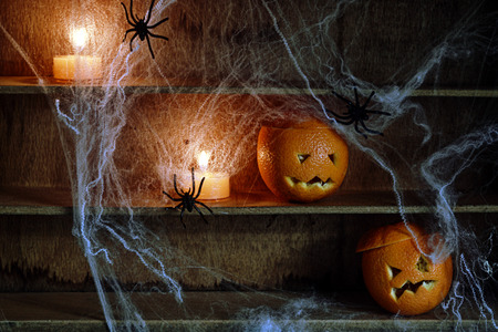 wood spider: Two Halloween Jack o Lanterns Carved from Oranges and Spiderwebs with Spiders and Lit Candles on Shelves