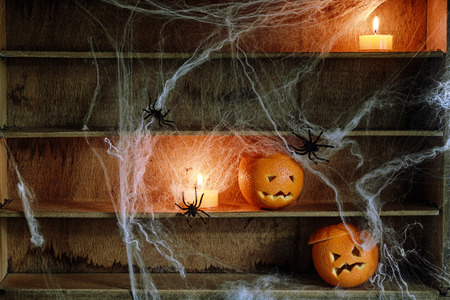 Two Halloween Jack o Lanterns Carved from Oranges and Spiderwebs with Spiders and Lit Candles on Shelves photo