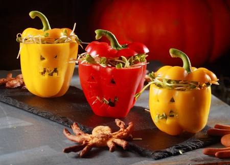 jack o lantern: Halloween themed salad with stuffed red and yellow sweet peppers with cutout faces like jack-o-lanterns served with a flying bat pastry on a curved bark plate