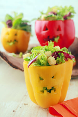 bell peppers: Colorful Halloween food background with creative stuffed red and yellow sweet bell peppers with faces cut into the skin like Halloween pumpkin lanterns filled with fresh green salad and cheese