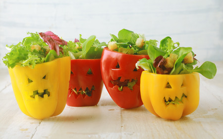 halloween: Colorful Halloween food background with colorful healthy stuffed red and yellow sweet bell peppers with cutout faces in the skin like Halloween jack-o-lanterns filled with green salad and cheese Stock Photo