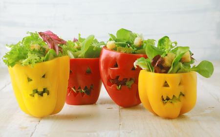 Kleurrijke Halloween voedsel achtergrond met kleurrijke gezond gevulde rode en gele zoete paprika met uitsparing gezichten in de huid, zoals Halloween jack-o-lantaarns gevuld met groene salade en kaas