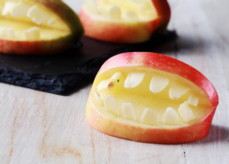 favor: Creative Halloween apple with teeth in a cutout shape with an open mouth for a healthy scary trick-or-treat favor Stock Photo
