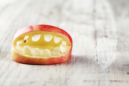 Scary Halloween apple mouth with bared teeth on a textured white background with copyspace for your greeting or invitation
