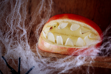 festooned: Ghoulish gaping Halloween mouth with teeth made from an apple on a wooden shelf festooned with spider webs in a scary festive background for Allhallows Eve