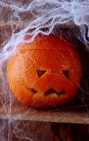 jackolantern: Spooky spider web covered jack-o-lantern formed from a fresh orange on a wooden shelf in a scary Halloween background Stock Photo