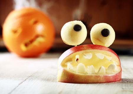 topped: Cute homemade Halloween apple decoration of an open mouth with teeth topped with googly dough eyes on toothpicks for a scary but healthy favor to give children trick-or-treating