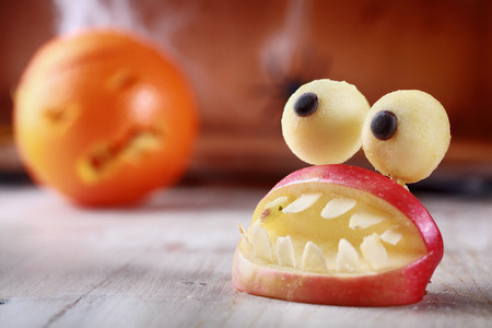 open topped: Fun scary homemade Halloween table decoration of fresh apple slices in the form of an open mouth with teeth topped by a pair of round googly dough eyes Stock Photo