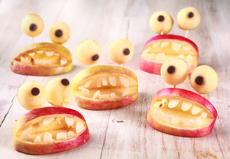 Spooky Halloween party favors or decorations made from fresh apples and dough in the form of open mouths lined with teeth topped with round googly eyes on a rustic table, creative country handicraft photo