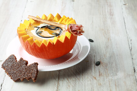 broomsticks: Pumpkin Soup with Bat Toast Crouton and Broomstick Bread Stick Served in Half a Pumpkin with Copyspace