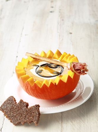 broomsticks: Pumpkin Soup with Bat Shaped Toast Crouton and Broomstick Bread Stick and Copyspace Stock Photo