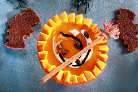 broomsticks: Halloween Pumpkin Soup Served in Half a Pumpkin with Bat Shaped Crouton Toasts and Broomstick Bread Stick from Above