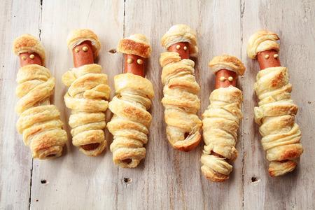 aliments droles: Six Weiners en croûte à ressembler à des momies Halloween sur fond de bois Banque d'images