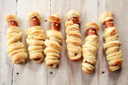 october 31: Six Weiners Wrapped in Pastry to Look Like Halloween Mummies on Wooden Background