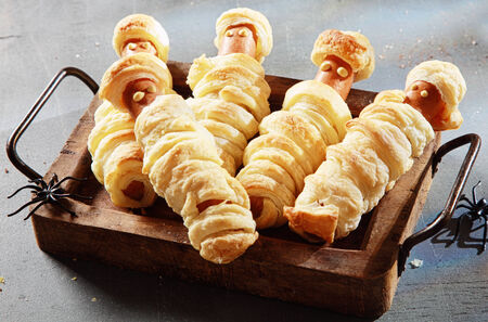 ghoulish: Five Weiner Mummies Wrapped in Pastry on Tray for Halloween Party Appetizer