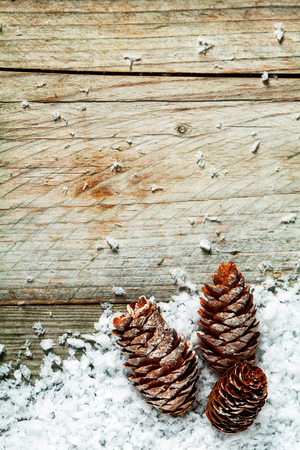 copyspace: Pine cone rustic Christmas background with three cones nestling in winter snow on old weathered wooden boards with plenty of copyspace for your Xmas message of good cheer