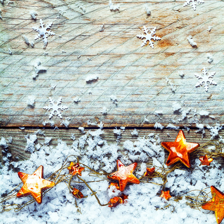 Golden stars with snow and falling snowflake decorations in a rustic Xmas background with copyspace for your Christmas greeting, square format