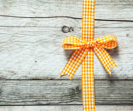 copyspace: Colorful orange and white festive rustic ribbon and bow decorating a background of old cracked weathered wooden boards with copyspace for your seasonal Christmas or birthday message