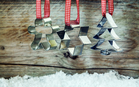 Christmas cookie cutter background with metal cutters shaped as a snowman , star and Christmas tree hanging from ribbons on an old wooden background with winter snow photo