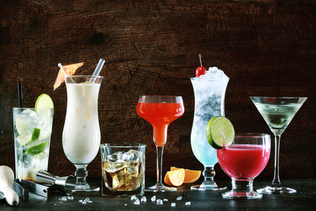 Selection of colorful festive Christmas drinks, alcoholic beverages and cocktails in elegant glasses on a dark background with copyspace Banco de Imagens