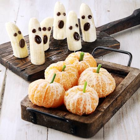 comida sana: Saludable de Halloween Treats Hecho en Los fantasmas de banano y Clementine Orange Pumpkins Foto de archivo