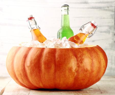 カボチャの氷のバケツで冷やしてボトル入りのアルコール飲料 写真素材