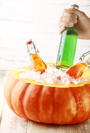 Hand Taking Cold Bottled Alcoholic Drink from Pumpkin Ice Bucket photo