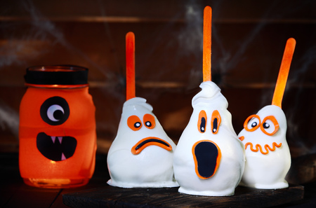 Delicious Halloween treat made of white chocolate coated pears next to a jar, all with funny scary faces photo