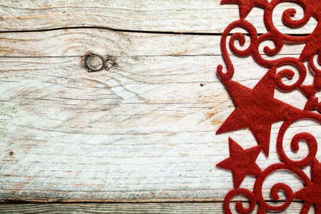 Decorative red star Christmas border with curlicues and swirls on the right side of a rustic wooden background with copyspace for your Xmas greeting