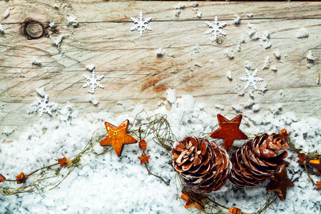 Seasonal Christmas background with pine cones draped in a garland of colorful orange stars sprinkled with winter snow against a rustic wooden background with snowflakes and copyspace