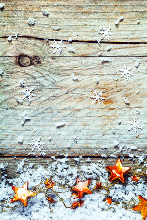 christamas: Garland of Christmas stars with snowflakes in a rustic Xmas background on old textured wood with cracks, knots and copyspace Stock Photo
