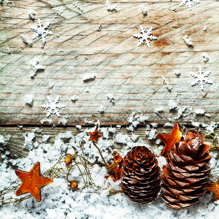 Traditional Advent or Christmas background with dried pine cones and golden orange stars in a bed of winter snow against old wooden boards decorated with snowflakes, square format photo
