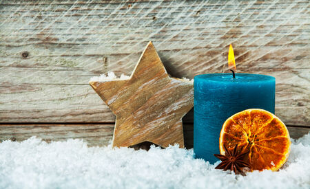Country Christmas background with a burning candle and hand crafted wooden star standing in winter snow with a dried orange slice against old wooden boards with copyspace photo
