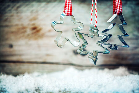 Rustic Xmas cookie cutters hanging from red and white ribbons above winter snow against an old wooden background with copyspace photo